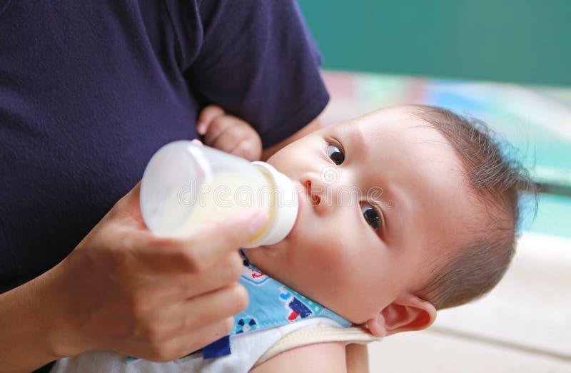 Latte alimentare neonato asiatico del primo piano dalla bottiglia tramite la madre immagini stock libere da diritti
