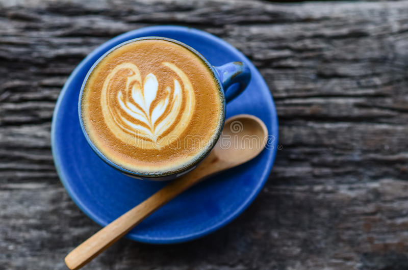 Latte art, Blue coffee cup. On wooden background royalty free stock photos