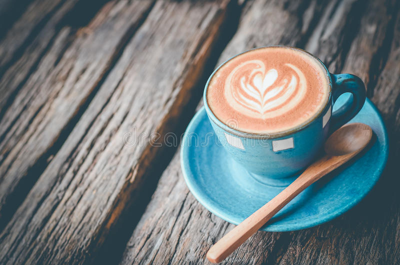 Latte art, Blue coffee cup on wooden background stock images
