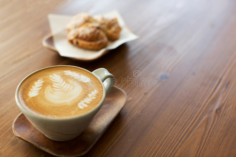 Latte art in cafe. Cup of latte coffee drink decorated with latte art and pastry at cafe royalty free stock photography