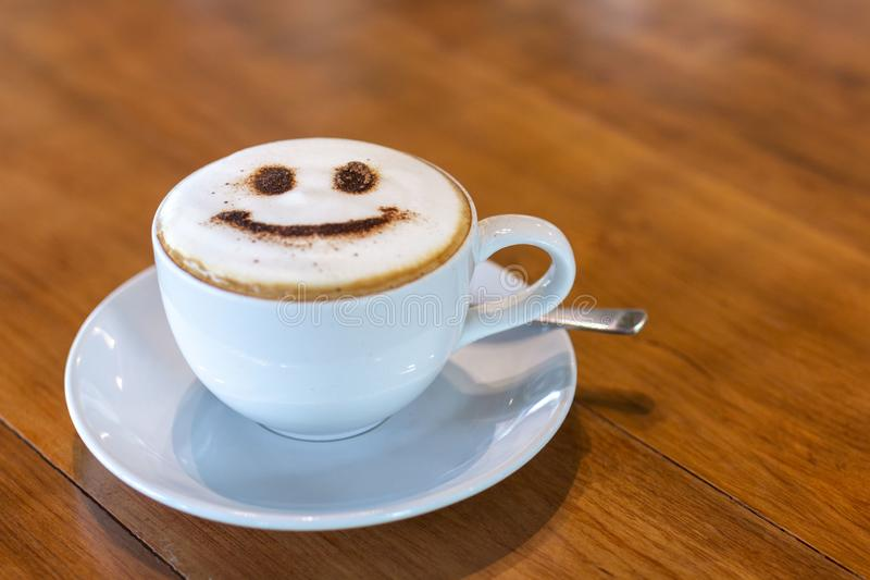 Latte art at cafe. White Cup of art latte on a cappuccino coffee. Cappuccino with smiley frothy foam, coffee cup top view closeup. Smile Coffee late art. A stock image