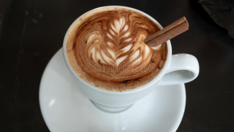 Latte Art on a Cappucinno. White cup of cappuccino on a wooden table. Cappuccino Latte Art. Espresso, milk stock photo