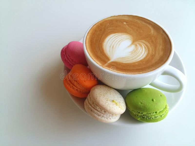 Latte art coffee so delicious with macaroon on white royalty free stock photos