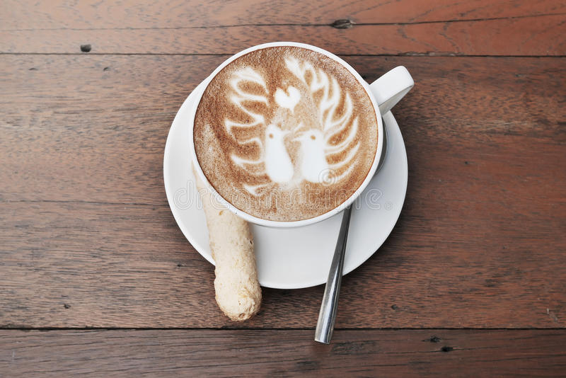 Latte art coffee with two birds pattern and cookie in a white cup royalty free stock photos