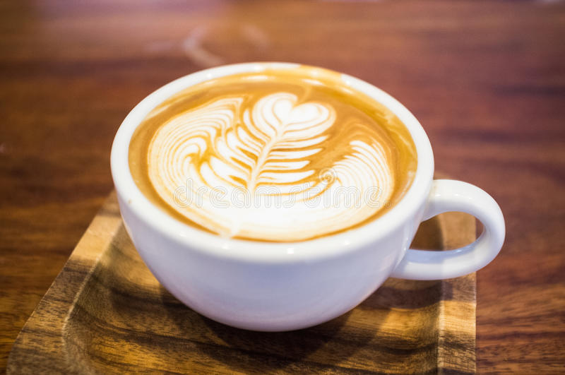 Latte art cup on wood plate royalty free stock photography