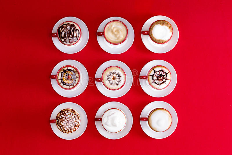 Latte art on a red background. Overhead view of striking patterns and latte art depicted in the foam on espresso or cappuccino coffee in red and white cups and stock image