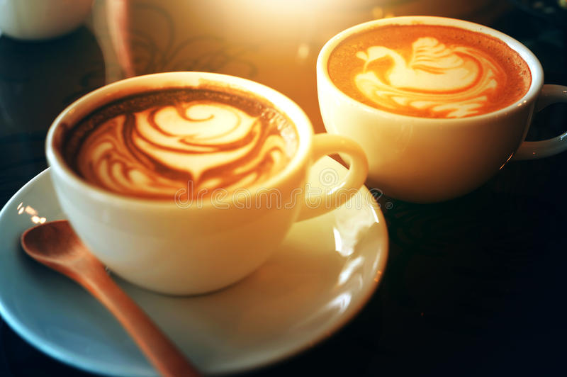 Latte art in swan and rose shape. On table stock image