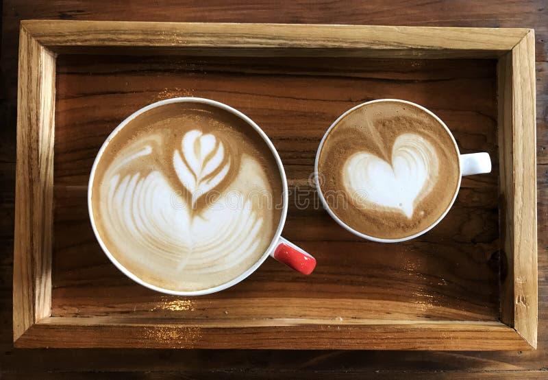 Latte blanco plano contra el latte de flautín en la taza blanca fotografía de archivo