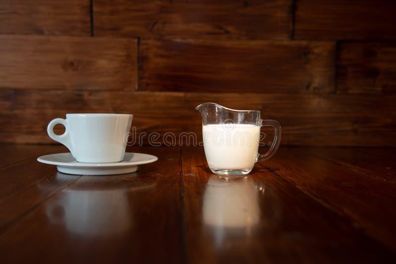 Latte in brocca di latte di vetro con la tazza bianca e riflessione da una tavola di legno immagine stock libera da diritti