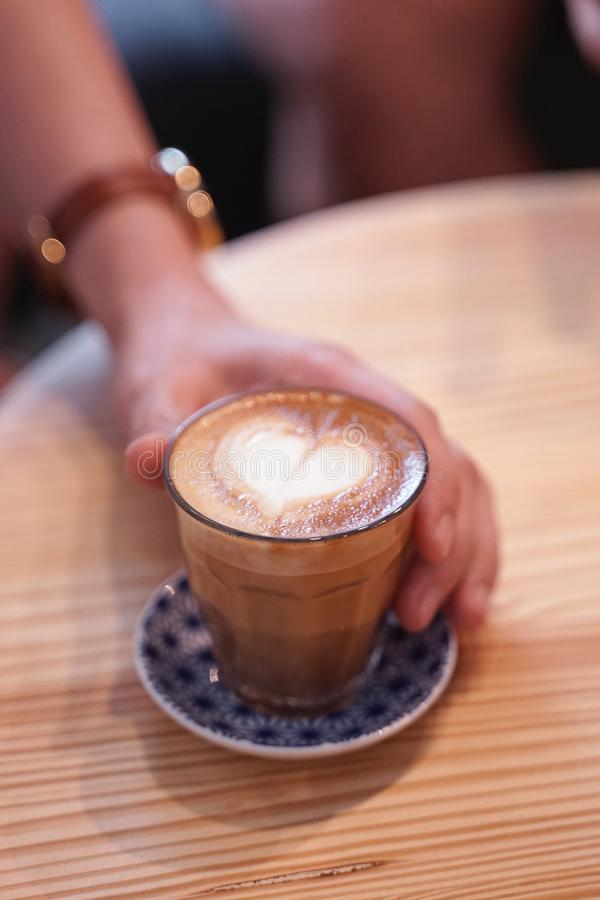 Latte caldo del caffè con arte del latte di forma del cuore in piccola tazza di vetro con la tenuta umana della mano fotografia stock
