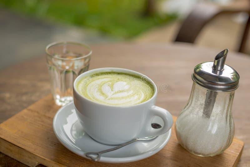Latte caliente de Matcha en la taza blanca con agua de la bebida en vidrio y azúcar en botella en la tabla de madera fotos de archivo libres de regalías