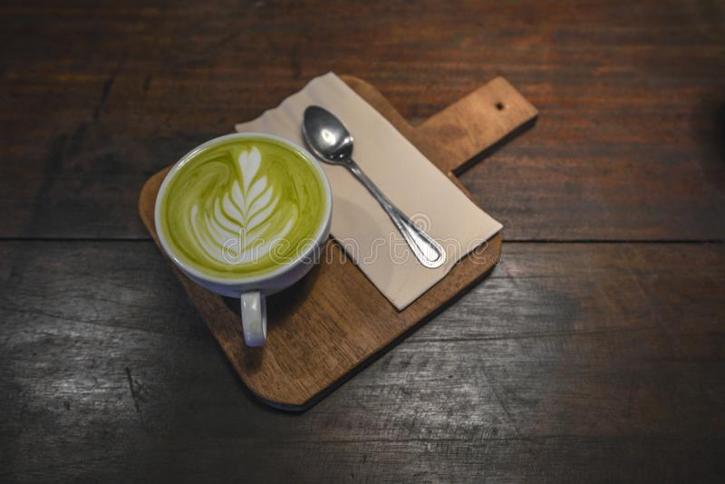 Latte caliente de Matcha en la taza blanca con la pequeña cuchara y servilleta en la tabla de madera foto de archivo libre de regalías