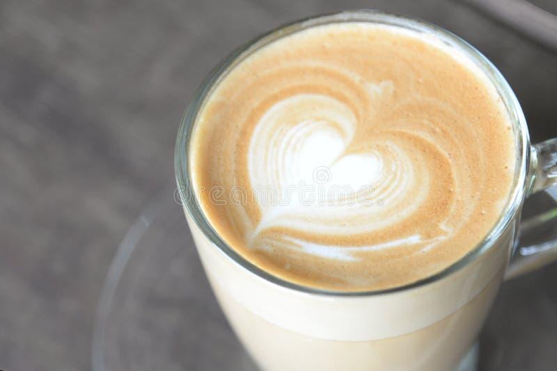 Latte caliente del caf? con forma hermosa del coraz?n del arte de la espuma en la tabla de madera en la cafeter?a fotografía de archivo