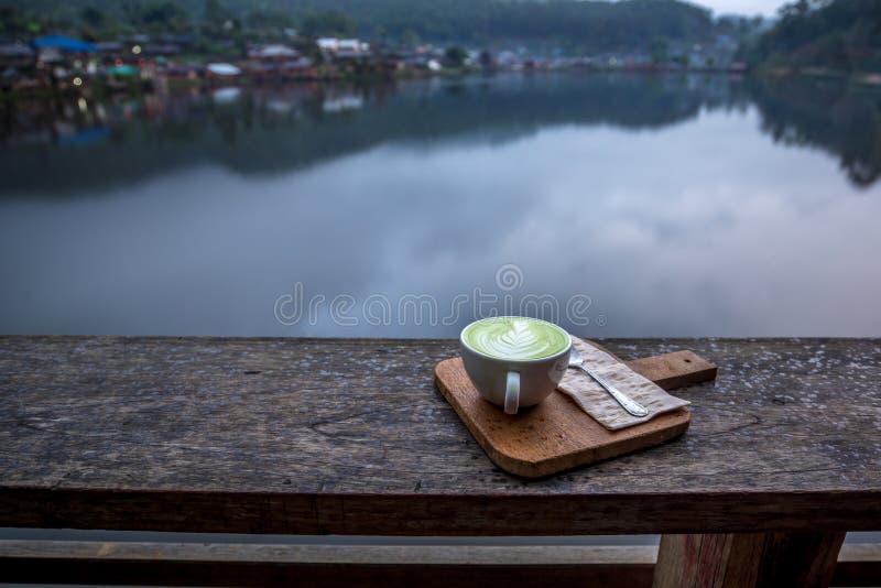 Latte caliente del té verde de Matcha en la taza blanca en el pórtico de madera con la opinión del río del pueblo foto de archivo libre de regalías