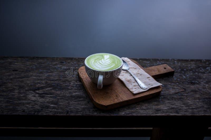 Latte caliente del té verde de Matcha en la taza blanca en el tablero de madera sobre el pórtico de madera con el río detrás fotos de archivo
