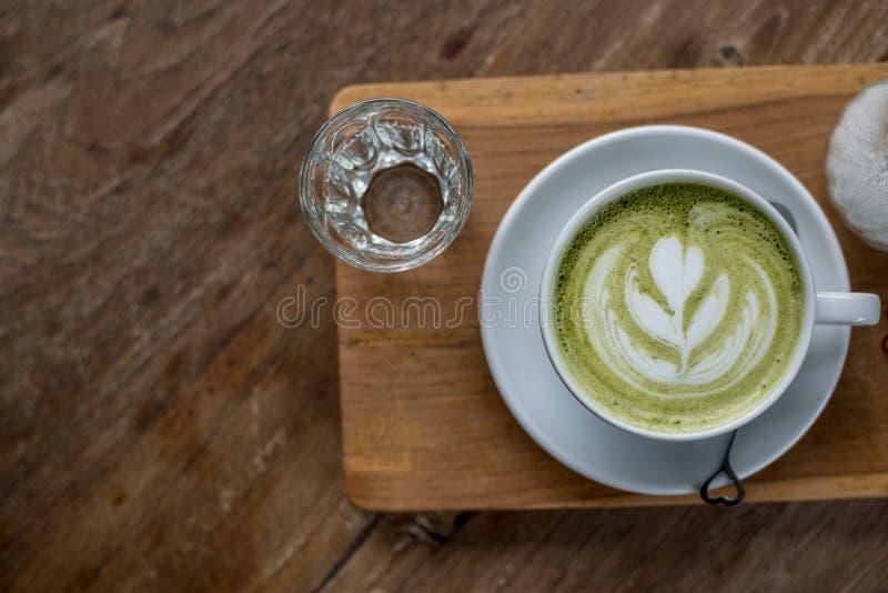 Latte caliente del té verde de Matcha en la taza blanca en la placa de madera con un poco de agua en vidrio en la tabla de madera imágenes de archivo libres de regalías