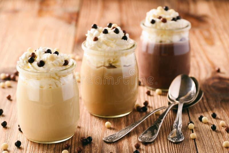 Latte, caramella e budino al cioccolato con panna montata su fondo di legno marrone fotografia stock libera da diritti