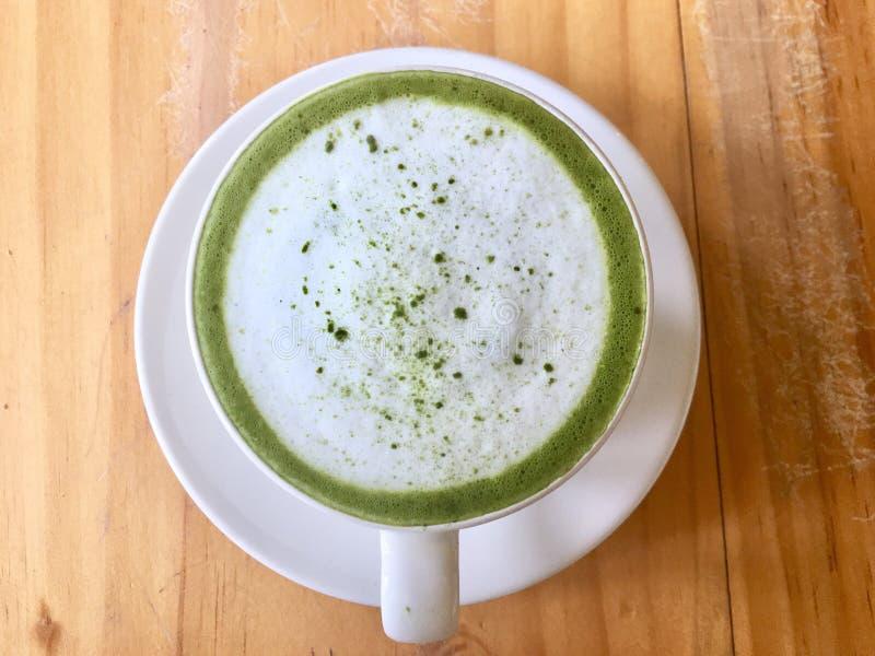 Latte chaud de matcha de thé vert dans la tasse blanche, boisson avec du lait d'isolement sur la table en bois images stock