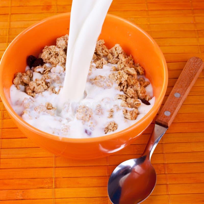 Latte che versa sul cereale fotografia stock libera da diritti