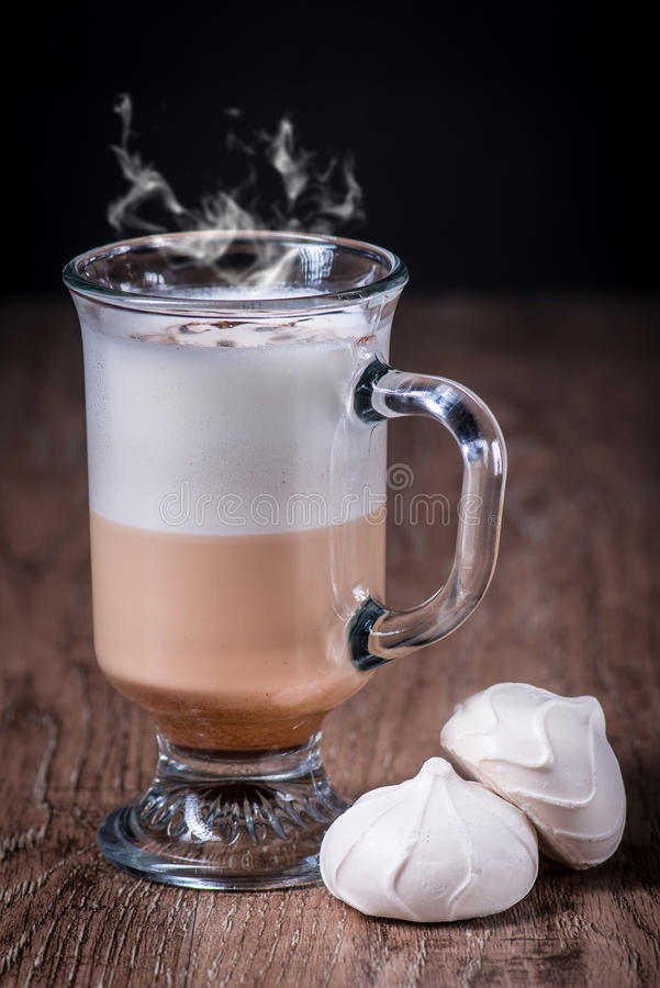Latte coffe glass with beans and meringue stock photography