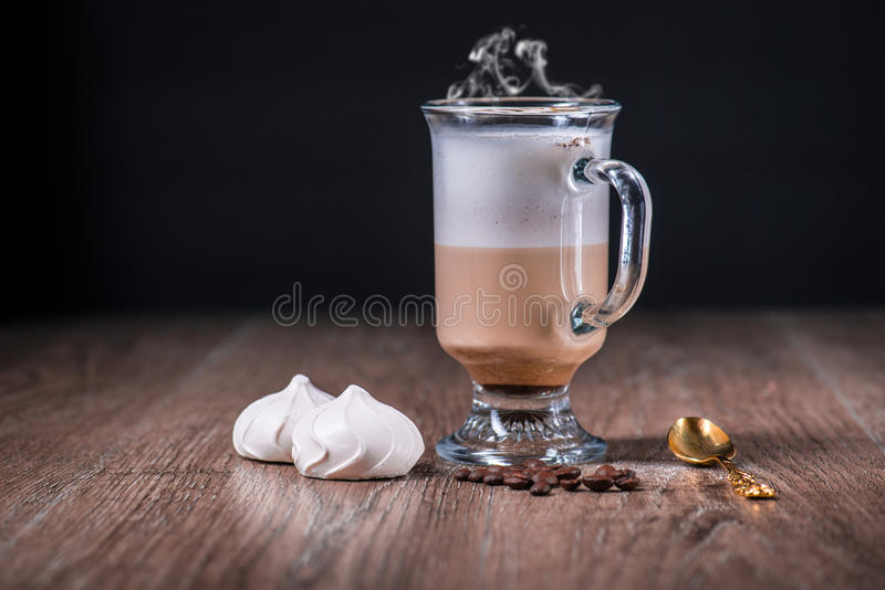 Latte coffe glass with beans and meringue stock images