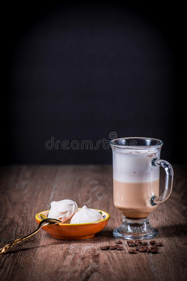 Latte coffe glass with beans and meringue stock photo