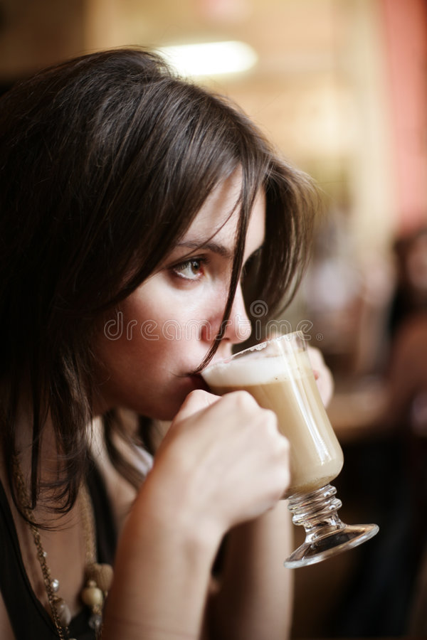 Latte coffee. Beautiful young girl sipping coffee latte. Shallow DOF