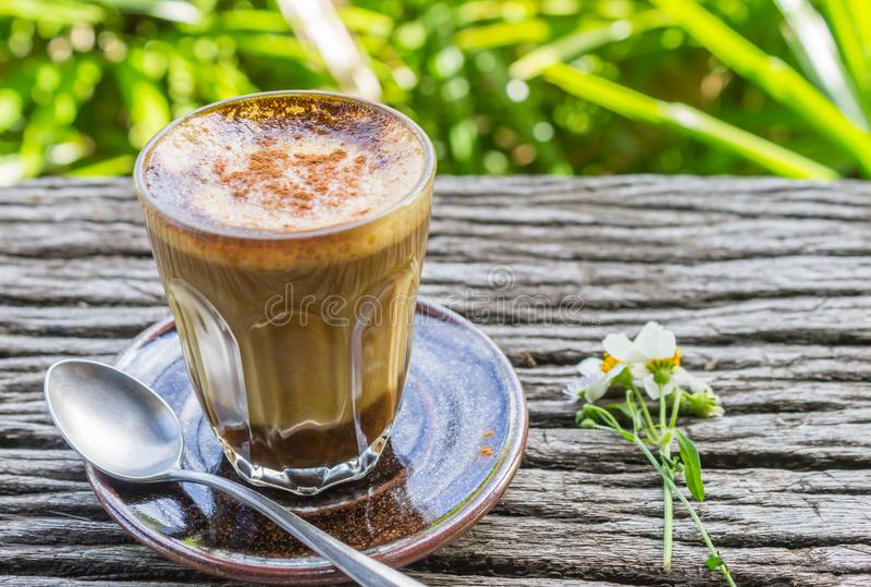 Latte Coffee and Daisy Flower and Spoon on Wood Table on Green T. Ree Background Left Zoom. Relax coffee break time in coffee shop on left frame royalty free stock image