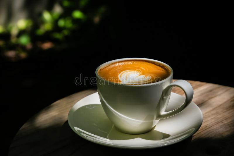Latte coffee on low light wood floors Natural light for design or background work royalty free stock image