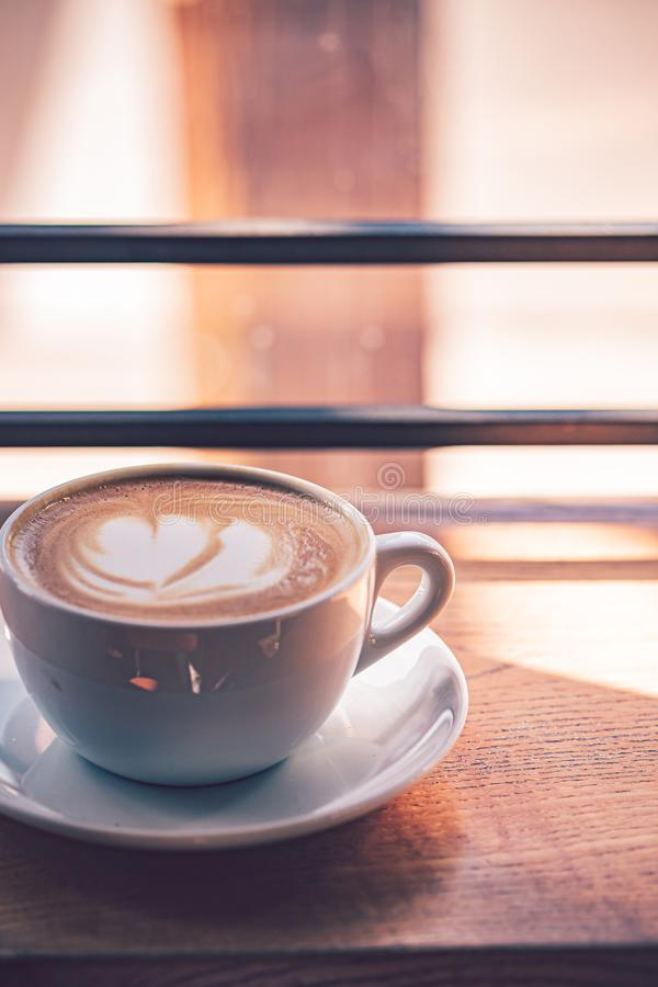 Latte coffee in white coffee cup on the wooden table in front of the large window of the coffee house.  royalty free stock image