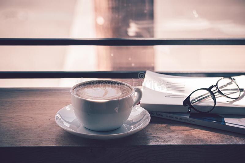Latte coffee in white coffee cup on the wooden table in front of the large window of the coffee house.  stock images