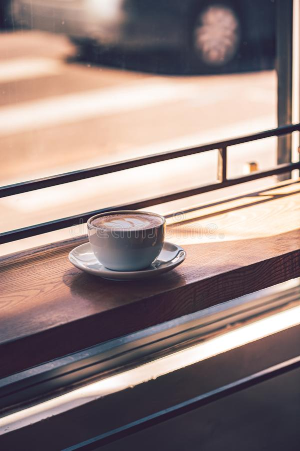 Latte coffee in white coffee cup on the wooden table in front of the large window of the coffee house.  stock image