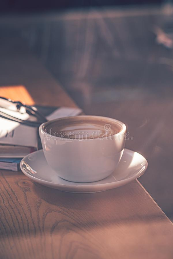 Latte coffee in white coffee cup on the wooden table in front of the large window of the coffee house.  stock photos