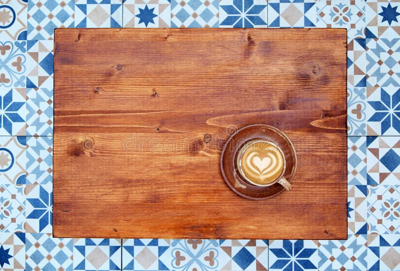 Latte coffee on wooden background top view. Cup of coffee on wooden table and mosaic tiles floor background. Fresh latte coffee on coffee table top view stock image
