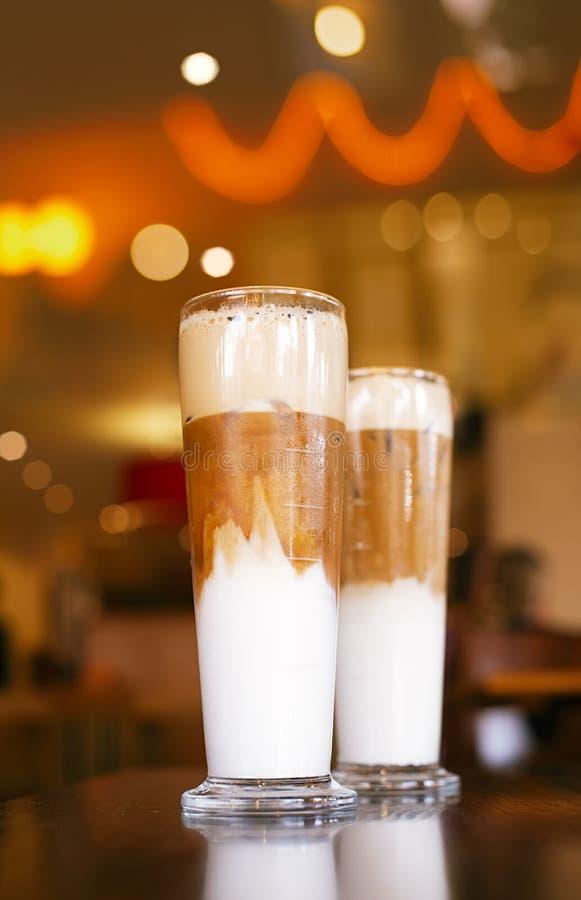 Latte congelado do café com luzes no fundo imagem de stock