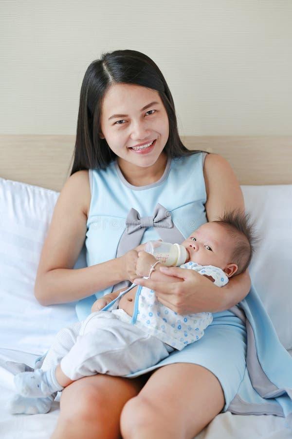 Latte d'alimentazione della bella madre asiatica il suo infante dalla bottiglia sul letto fotografie stock libere da diritti