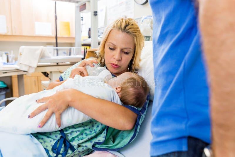 Latte d'alimentazione della donna al neonato sul letto di ospedale fotografia stock