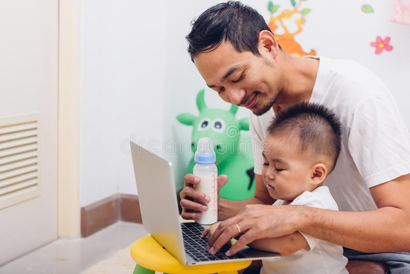 Latte d'alimentazione della mamma sostituta del padre il suo bambino di 1 anno del bambino del figlio mentre lavorando al compute fotografia stock libera da diritti