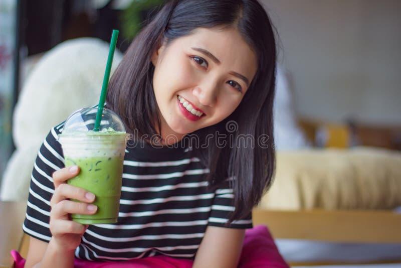Latte de consumición sonriente del té verde del matcha de la mujer por la mañana en la cafetería Muchacha asiática bonita del ret imagenes de archivo
