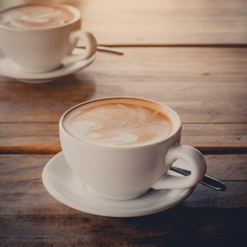 Latte de duas xícaras de café na tabela de madeira fotografia de stock