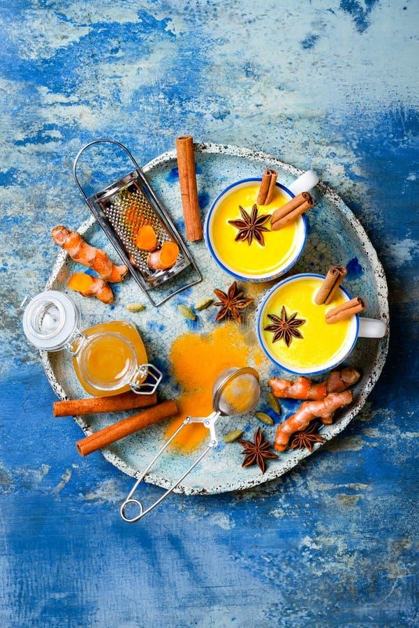 Latte de oro de la leche de la c?rcuma con los palillos y la miel de canela Detox, impulso inmune, bebida acogedora sana inflamat fotografía de archivo libre de regalías