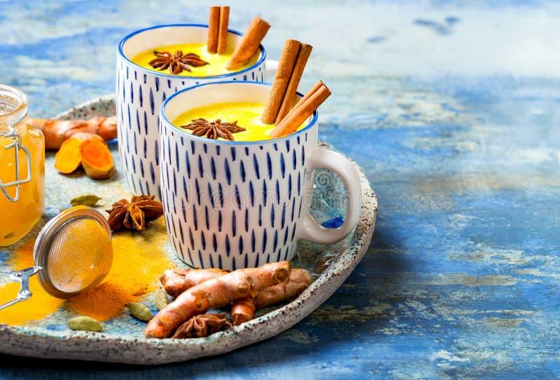 Latte de oro de la leche de la c?rcuma con los palillos y la miel de canela Detox, impulso inmune, bebida acogedora sana inflamat imágenes de archivo libres de regalías