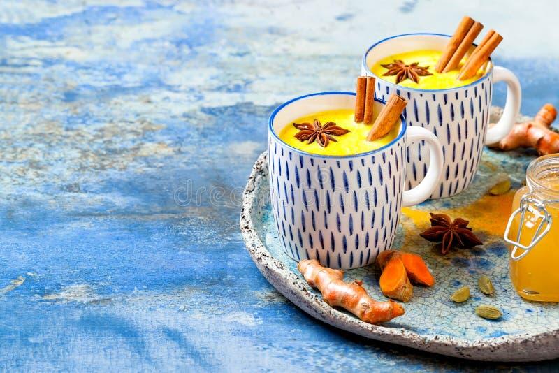 Latte de oro de la leche de la c?rcuma con los palillos y la miel de canela Detox, impulso inmune, bebida acogedora sana inflamat imagenes de archivo