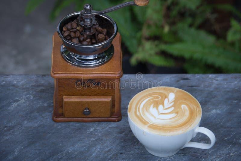 Latte del caffè con il chicco d'annata di caffè e del macinacaffè fotografia stock