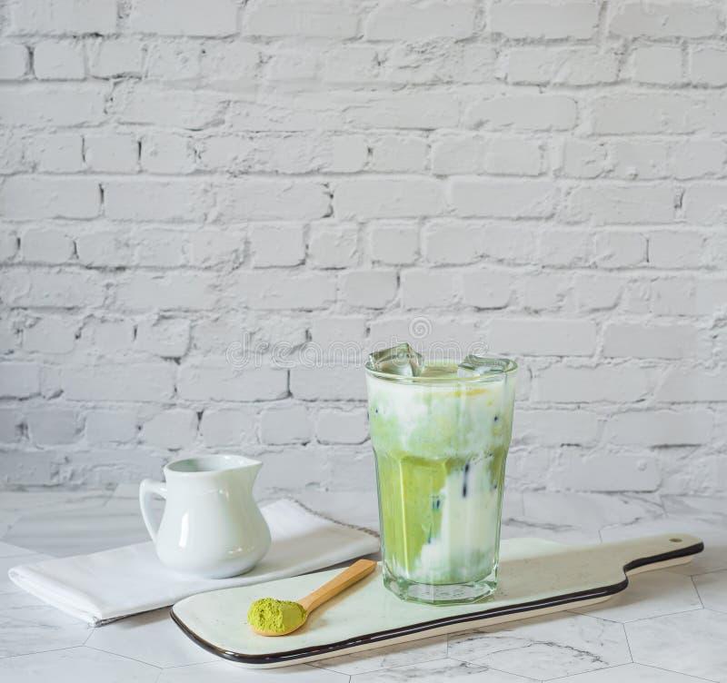Latte del tè verde di Matcha con la polvere di matcha ed il cucchiaio di legno fotografie stock libere da diritti
