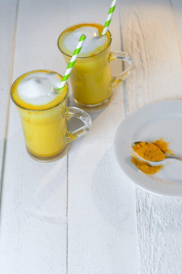 Latte della curcuma o latte dorato in vetri su una tavola bianca immagine stock libera da diritti