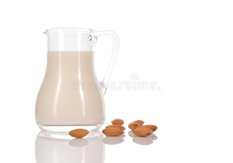 Latte della mandorla in brocca su fondo bianco fotografie stock