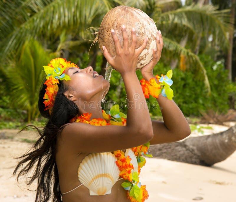 Latte di noce di cocco bevente della donna fotografia stock