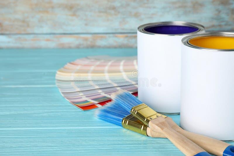 Latte di pittura, delle spazzole e dei campioni della tavolozza di colore sulla tavola di legno blu fotografia stock