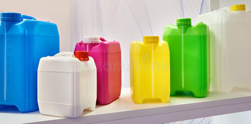 Latte di plastica variopinte vuote per i liquidi in deposito fotografia stock libera da diritti